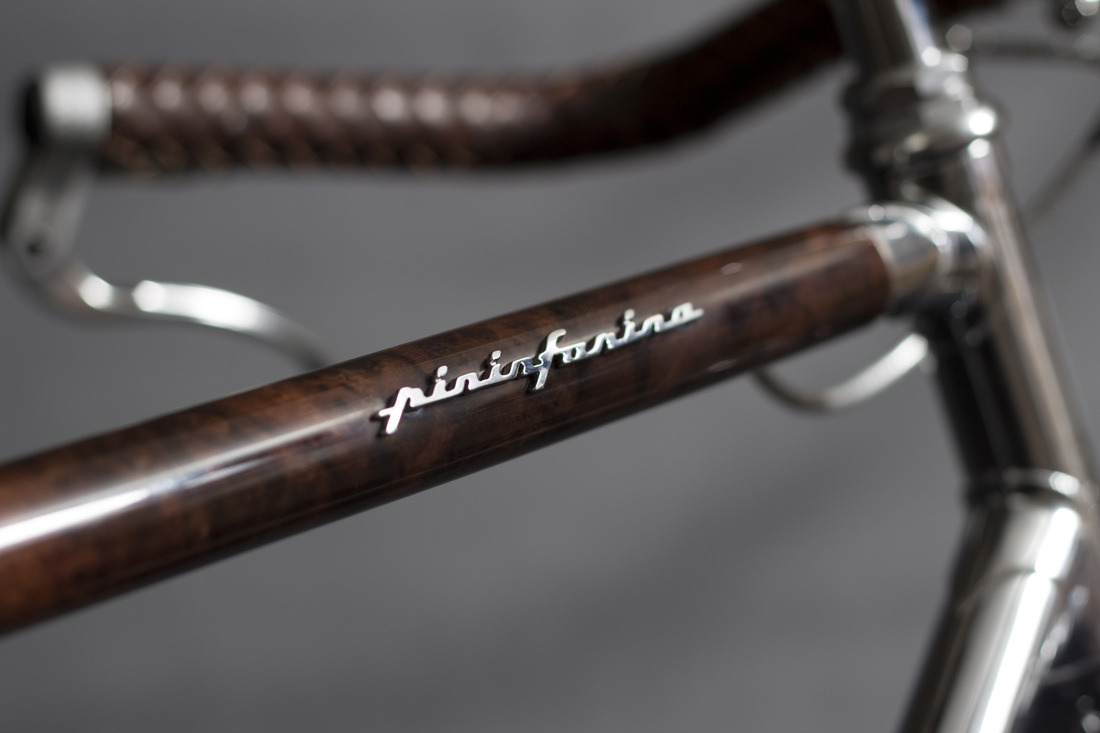 Il rivestimento in radica di noce sul tubo orizzontale e il logo Pininfarina!