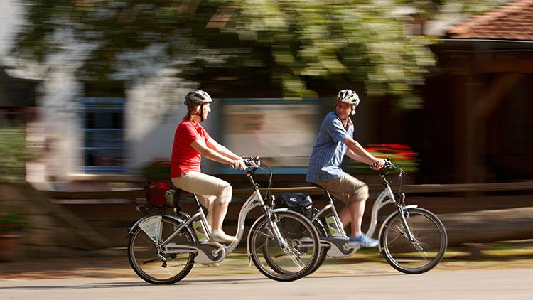 Due maturi ciclisti in sella a biciclette elettriche