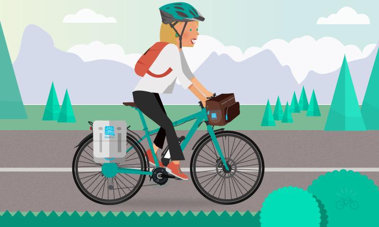 Una donna in sella ad una emtb equipaggiata con borse per lunghi viaggi