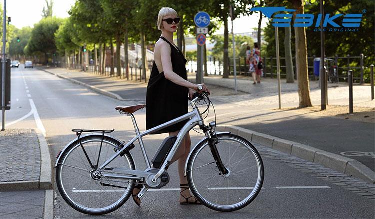 Una bicicletta elettrica Ebike Das Original Sport Daytona portata a mano da una donna