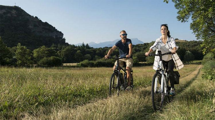 Due ciclisti soddisfatti pedalano in sella a due bici elettriche Brinke