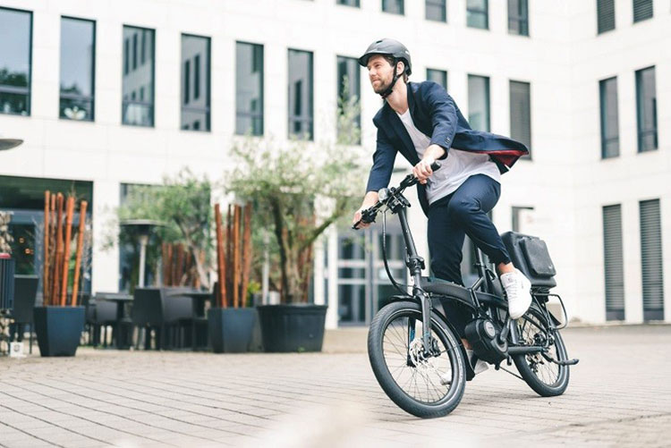 Un commuter urbano felice in sella a una ebike Tern Vektron