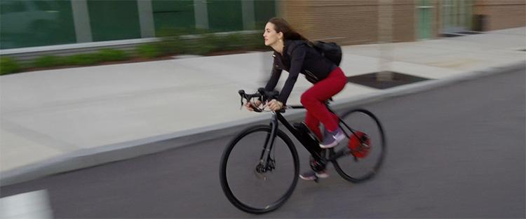 Una donna pedala in sella a una bici equipaggiata col kit Falco eDrive