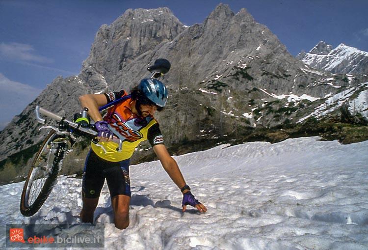 foto di un ciclista nella neve con mtb in spalla