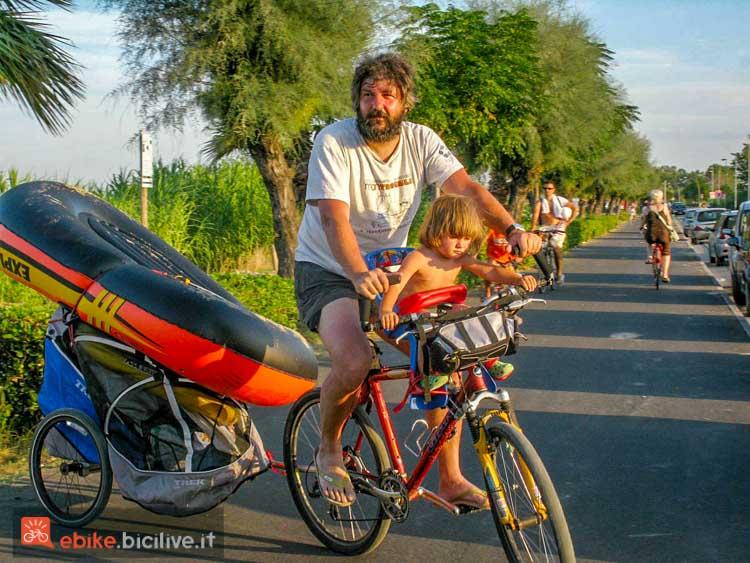 foto di un ciclista con carrellino al seguito e bimbo sul seggiolino