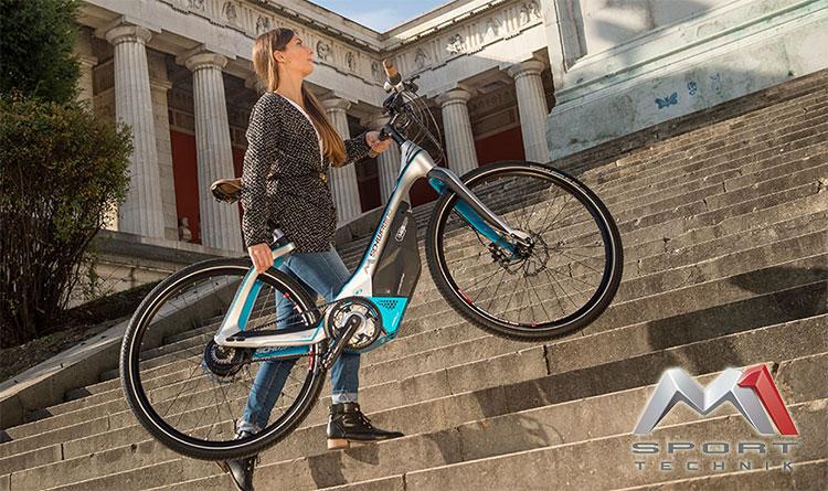 Una bici elettrica Das Schwabing trasportata per le scale da una ragazza