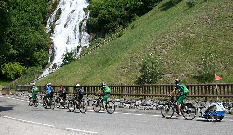 ciclisti pedalano vicino a una cascata del trentino
