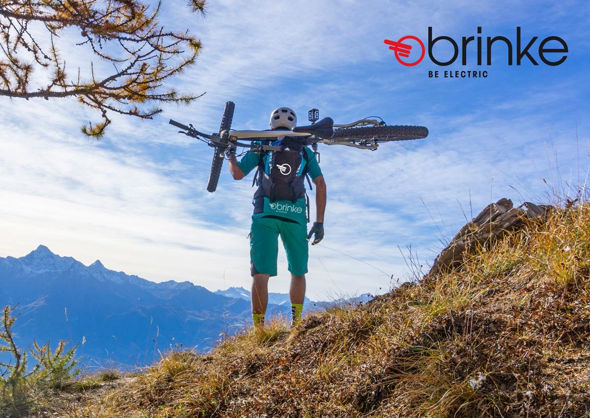 Ciclista in montagna con una ebike Brinke in spalla