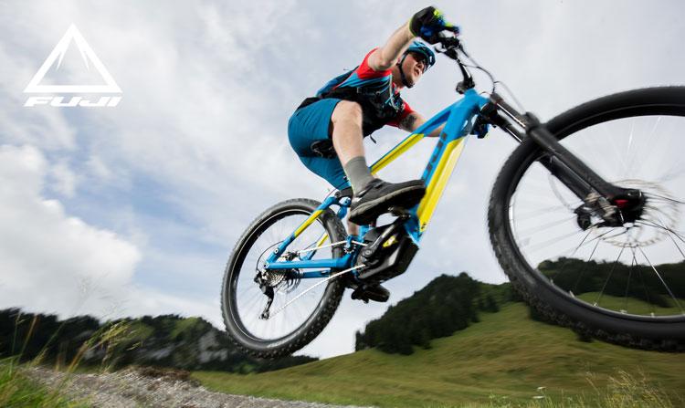 Un ciclista in salto in sella a una ebike Fuji del catalogo 2018