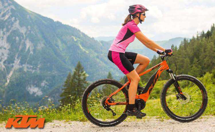 Una rider donna in sella a una mountain bike a pedalata assistita KTM