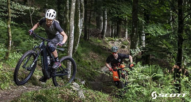 Una coppia di rider nel bosco su mtb elettriche Scott