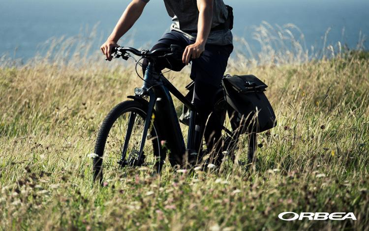 Un ciclista pedala nei prati su una ebike Orbea Keram