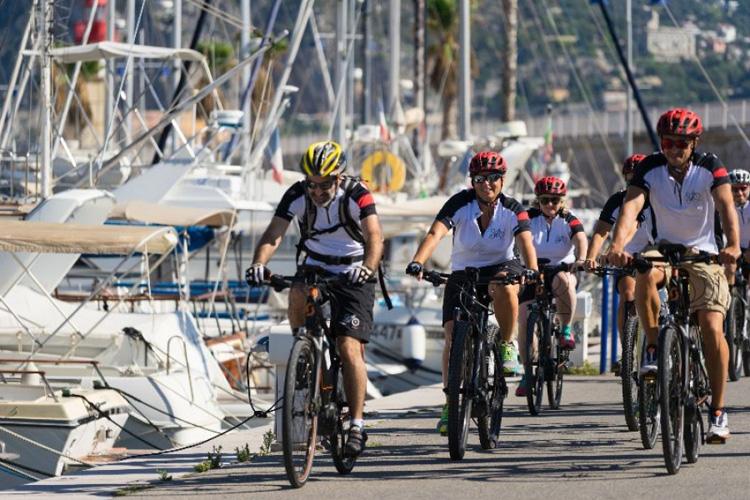 Cicloturisti sorridenti in sella a bici elettriche al porto