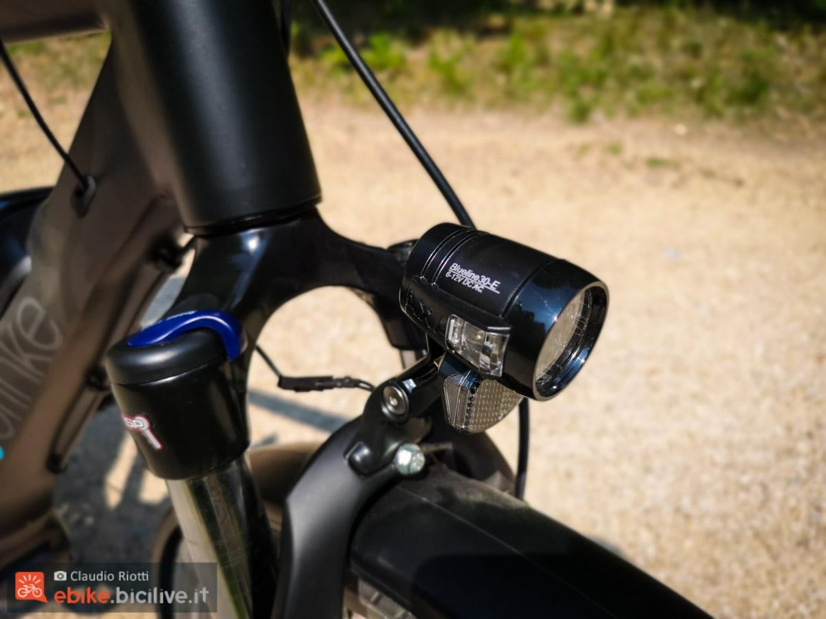 foto del potente faro anteriore Blueline e la forcella ammortizzata Suntour dotata di blocco e regolazione del precarico della molla.
