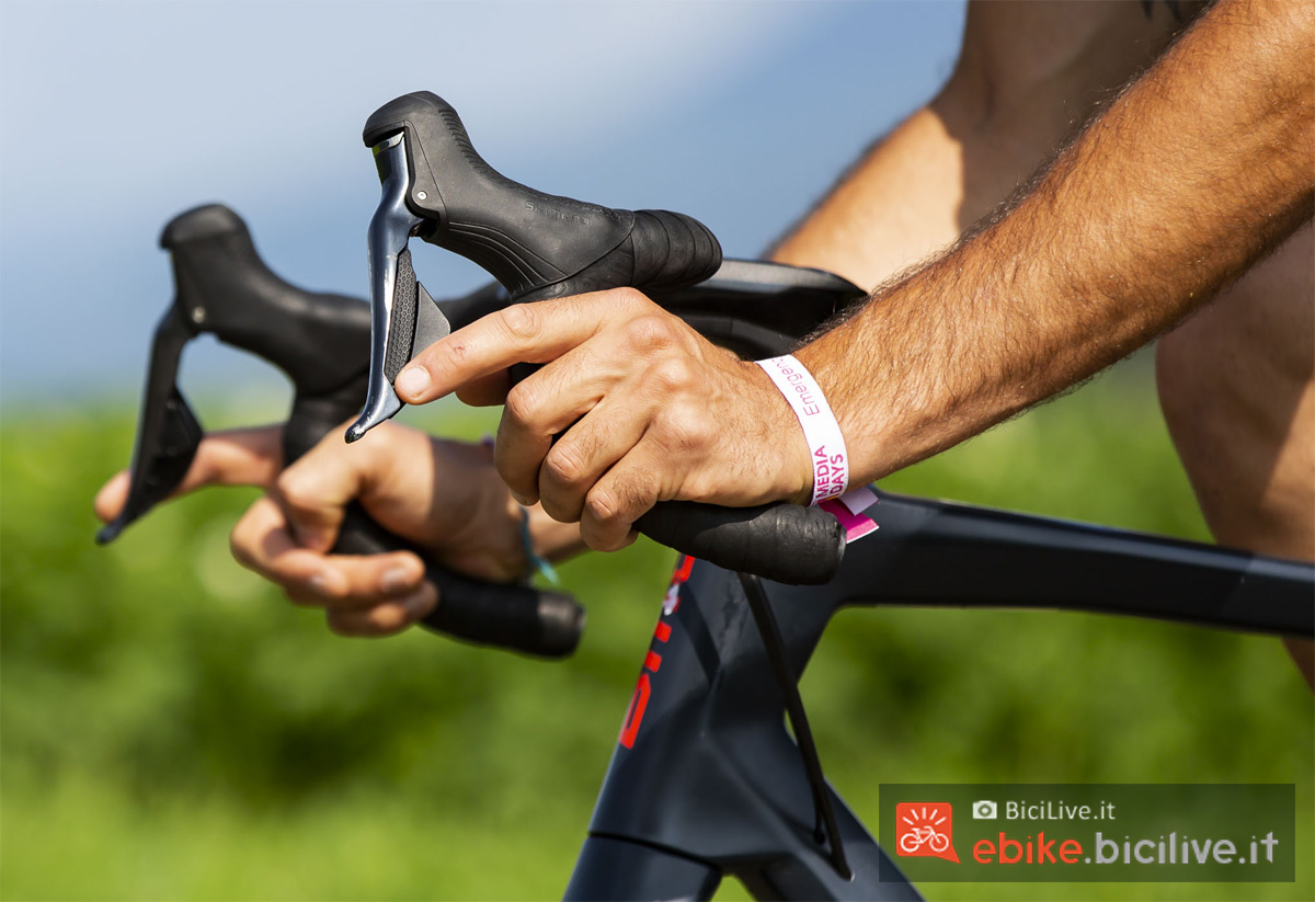 Le mani di un ciclista saldamente aggrappate al manubrio di una bici elettrica da corsa