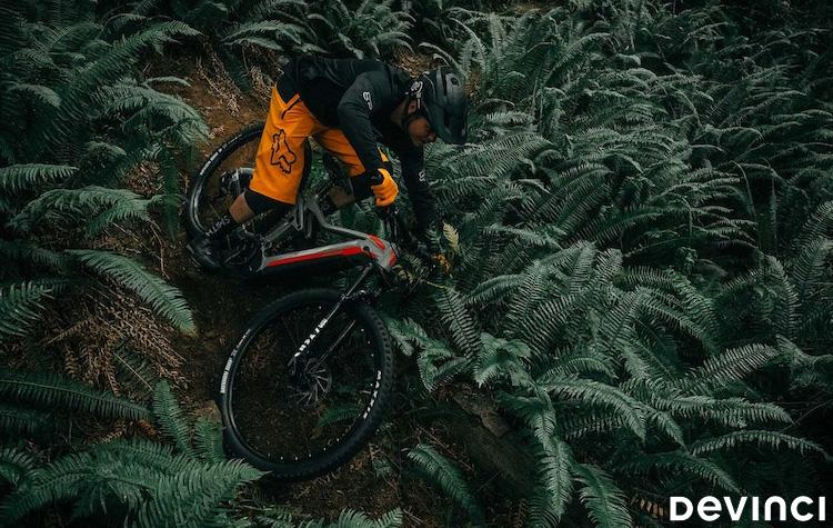 Un rider nel bosco in sella a una ebike Devinci 2020