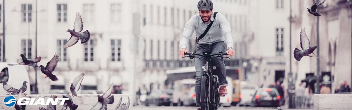 Ciclista felice in sella a una ebike Giant 2020 in città
