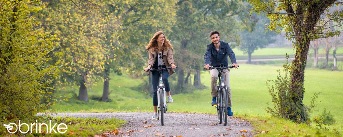 Coppia pedala felice in sella a bici elettriche Brinke