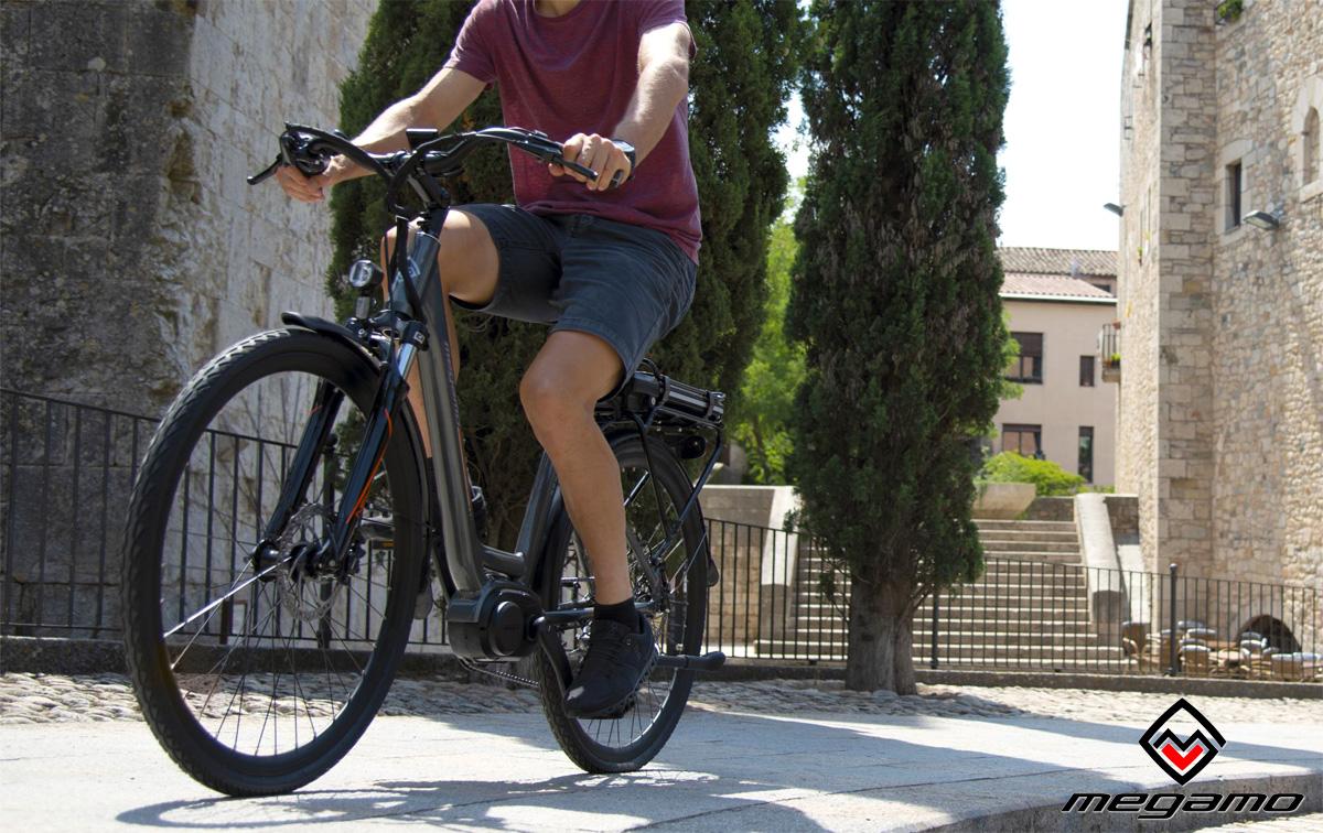 Ciclista a spasso per la città su una city ebike Megamo