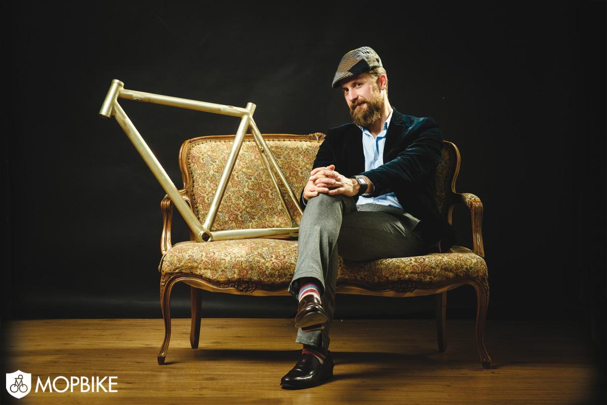 Massimo Ottavio Pavan seduto su un divano con il telaio di una bicicletta