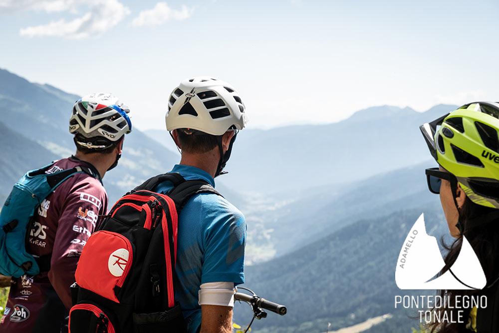 Tre cicloturisti osservano il panorama montano che li circonda