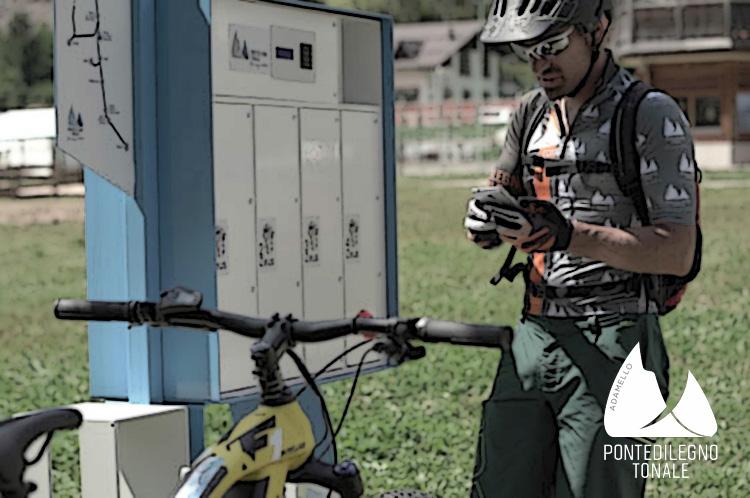 Cicloturista ricarica la sua ebike a una colonnina a Ponte di Legno Tonale