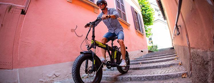Ciclista urbano scende dei gradini su una ebike pieghevole Atala
