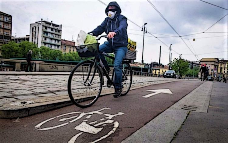 Ciclista urbano pedala per Milano indossando una mascherina contro il Covid-19