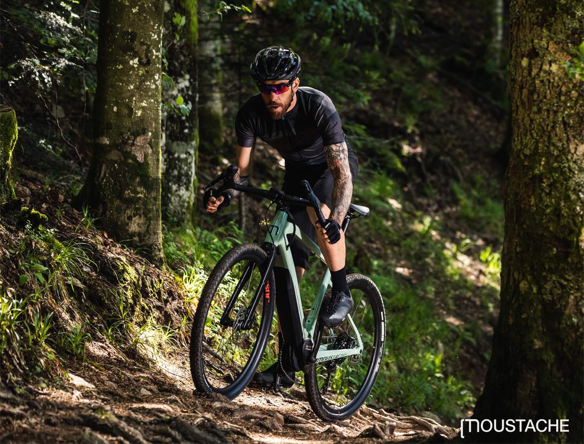 Un ciclista pedala nel bosco in sella a una bici elettrica Moustache Dimanche 29
