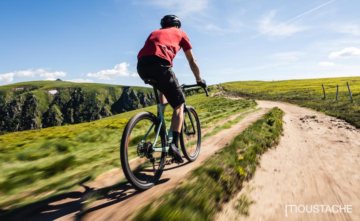 Un ciclista pedala su un sentiero sterrato in sella a una bici elettrica Moustache Dimanche 29