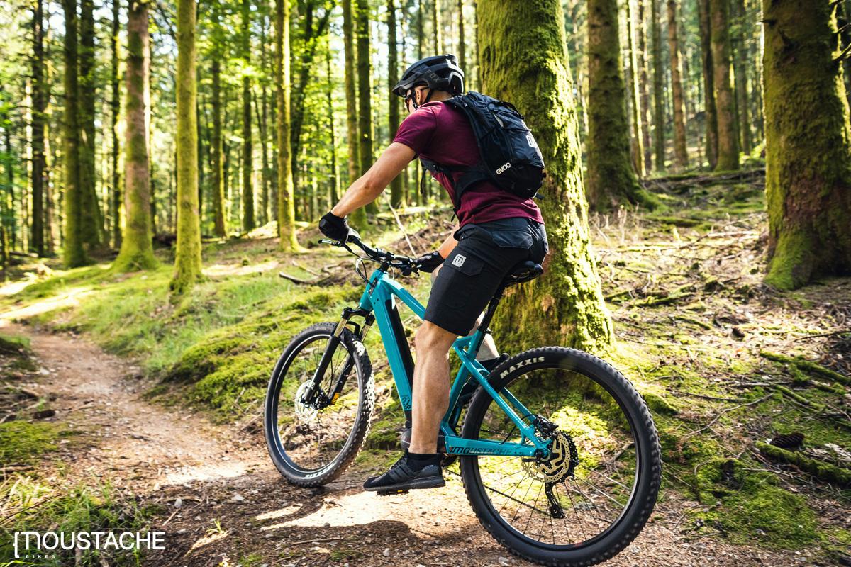 Rider pedala nel bosco in sella a una mtb elettrica Moustache 2020