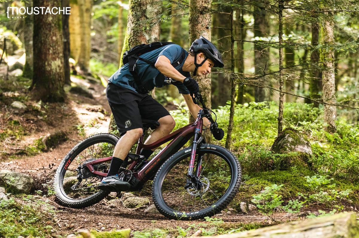 Rider si diverte su un sentiero nel bosco in sella a una e-MTB Moustache 2020