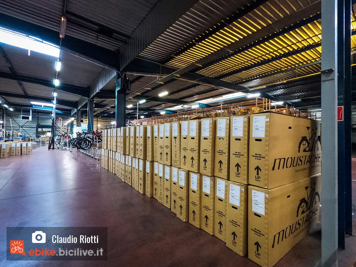 Magazzino Moustache Bikes con impilate le scatole delle e-bike pronte per la spedizione