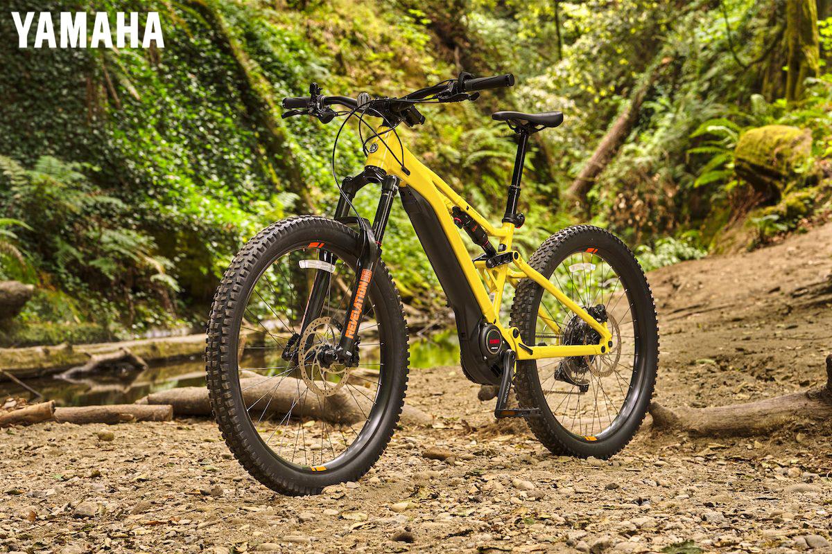 La nuova bici elettrica Yamaha YDX-Moro in colorazione gialla su un sentiero in un bosco