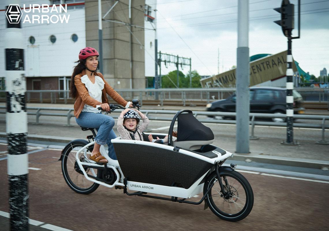 Una ragazza pedala in sella alla Family Cargo Line Disc Zee 500Wh, trasportando il suo bambino nel box