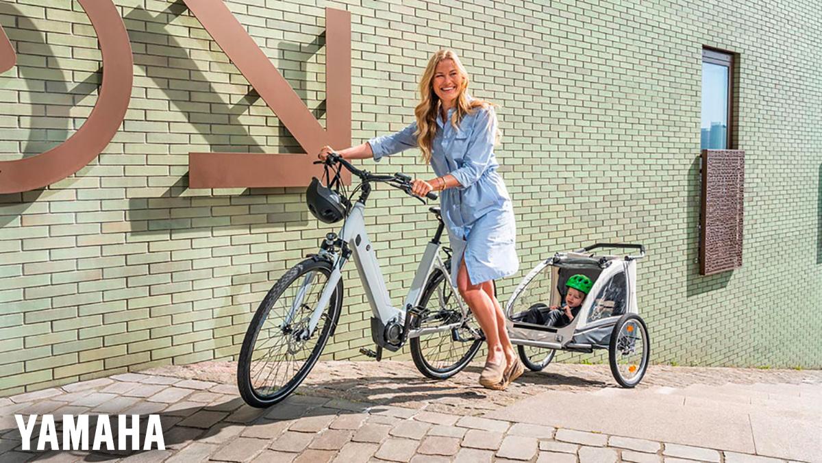 Una mamma spinge la sua e-Bike con rimorchio dove c'è un bimbo