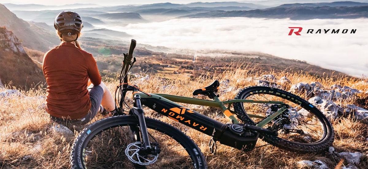 Una donna ammira il panorama con al fianco la sua nuova ebike R-Raymon 2021