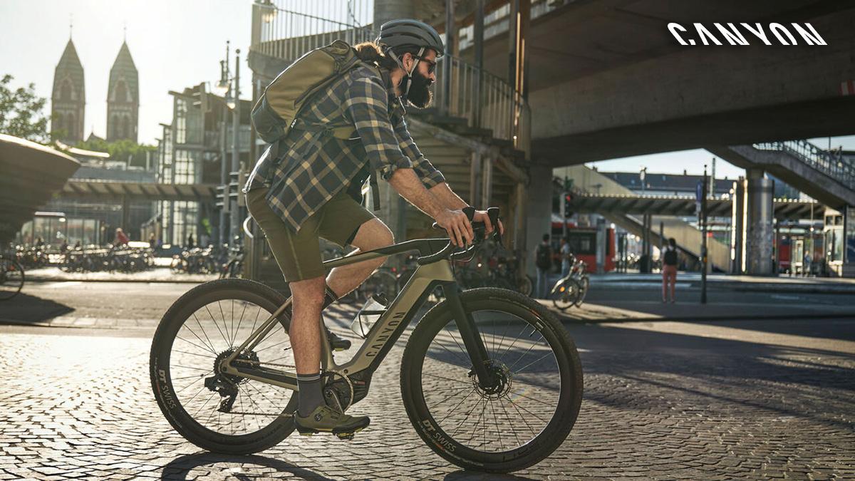 Un uomo pedala in città in sella alla nuova ebike Canyon Grail:ON 2021