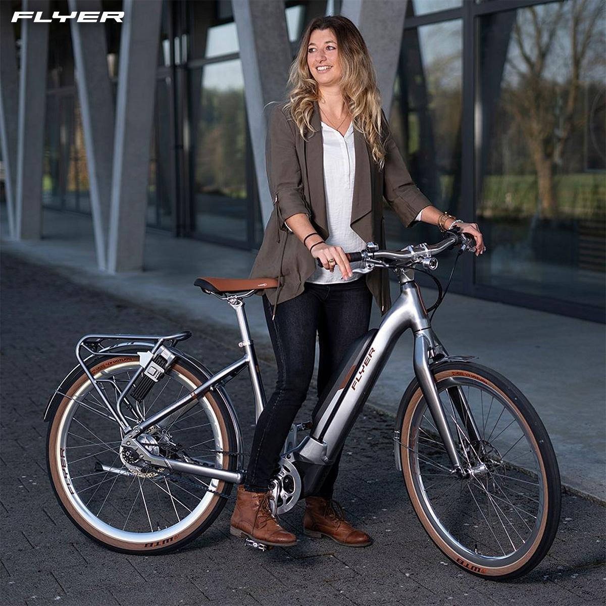 Una donna in sella alla propria nuova city bike elettrica Flyer Upstreet5 Anniversary Edition 2021