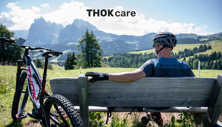 Ciclista si rilassa seduto su una panchina insieme alla sua eMTB Thok