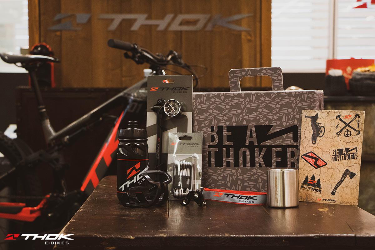 Accessori ciclista e valigetta Thok esposti su un tavolo