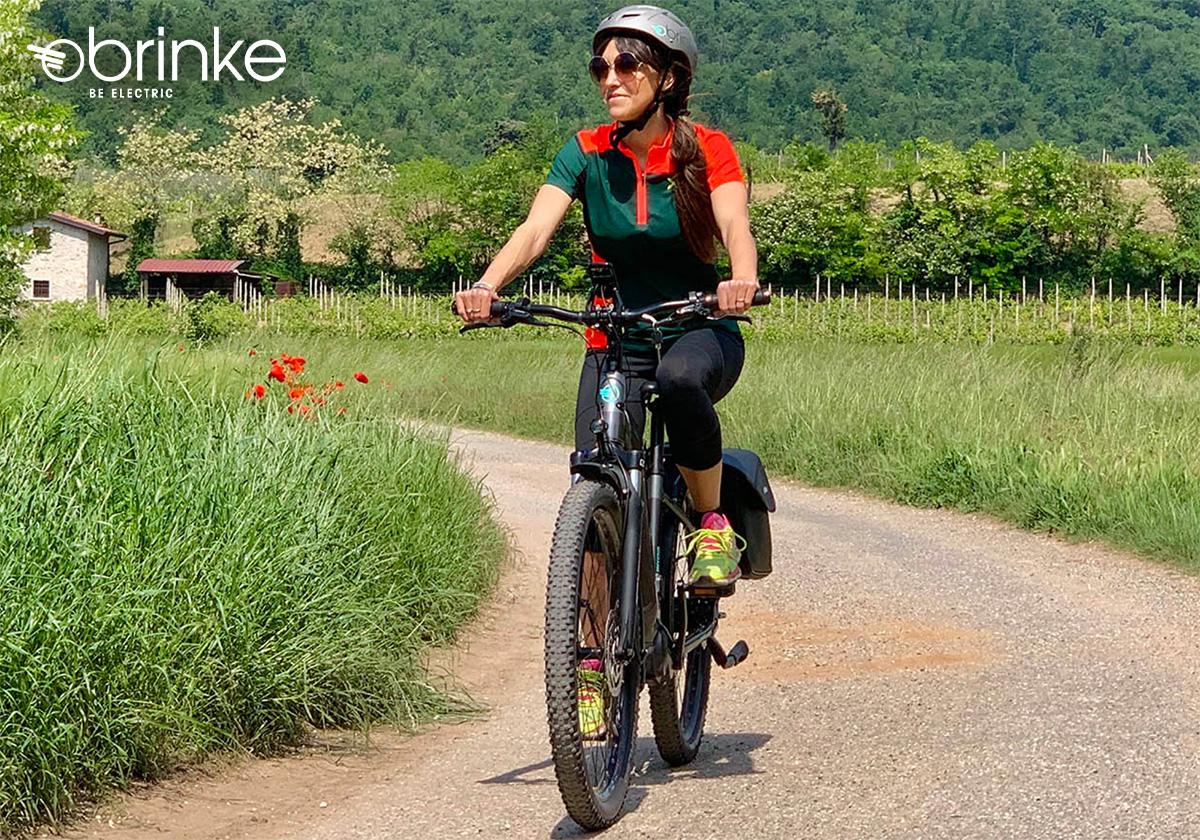Un ragazza pedala su un percorso sterrato con la sua bici elettrica trekking 2021