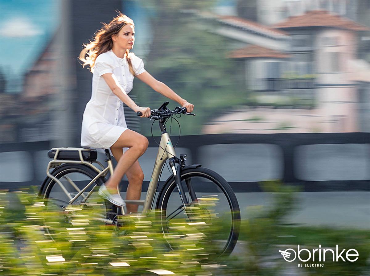 Una ragazza pedala in sella ad una nuova city ebike Brinke 2021