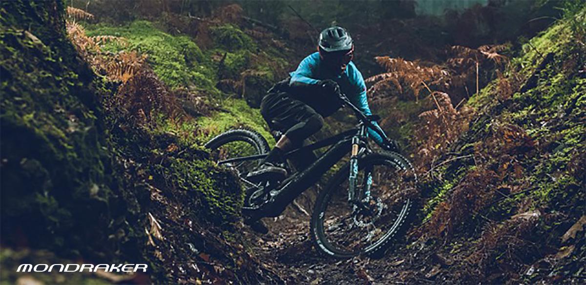 Un rider pedala nel bosco in sella ad una nuova emtb Mondraker 2021