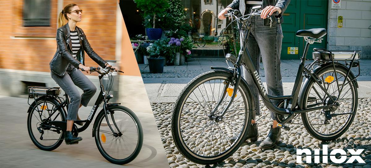 Una donna a spasso per la città in sella a una bici elettrica Nilox J5 gamma 2021