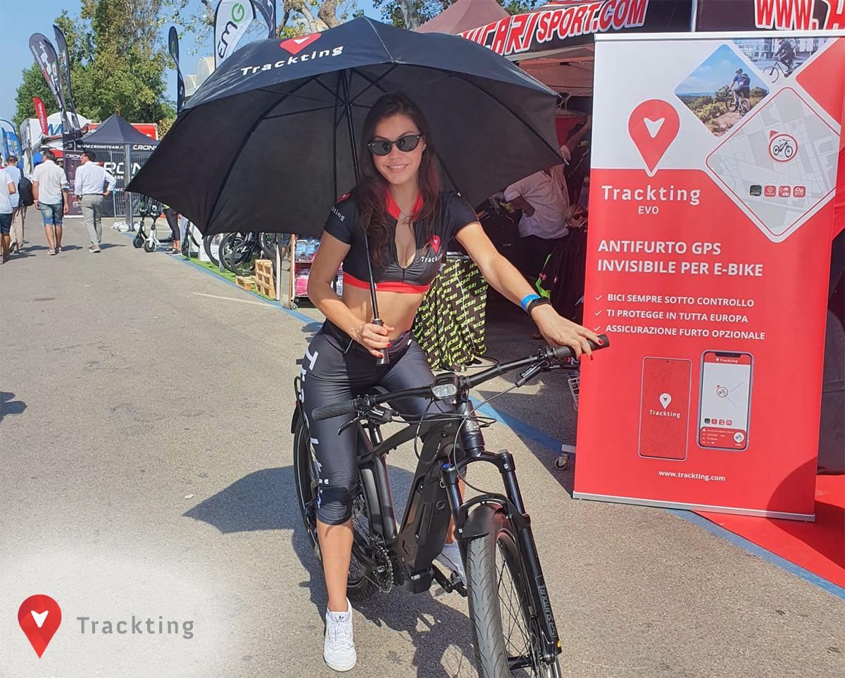 Una ragazza con l'ombrello ferma su una bici davanti allo stand di Trackting