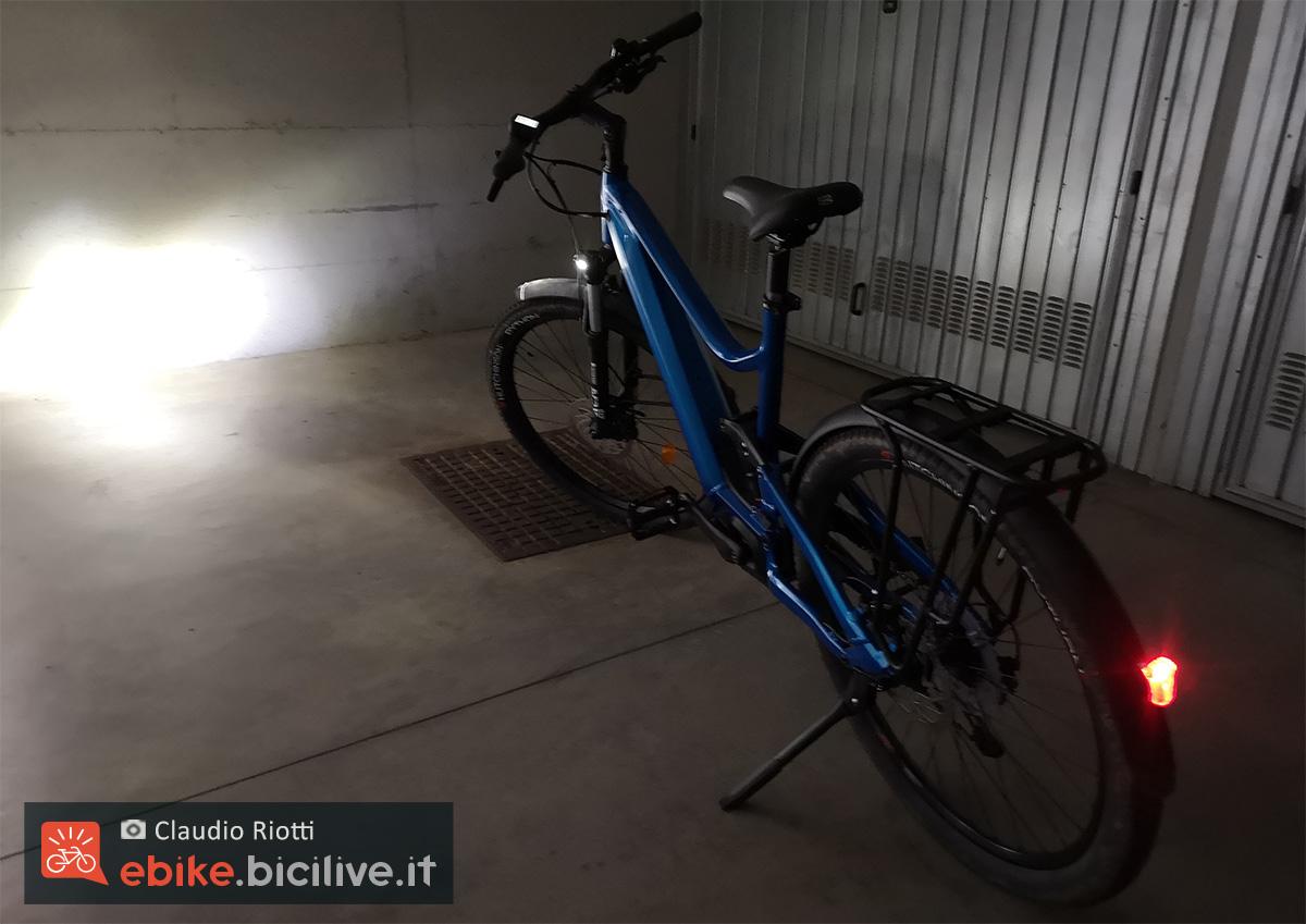 Il potente faro anteriore della ebike trekking Moustache Samedi 27 Xroad FS3 2021 illumina un garage buio