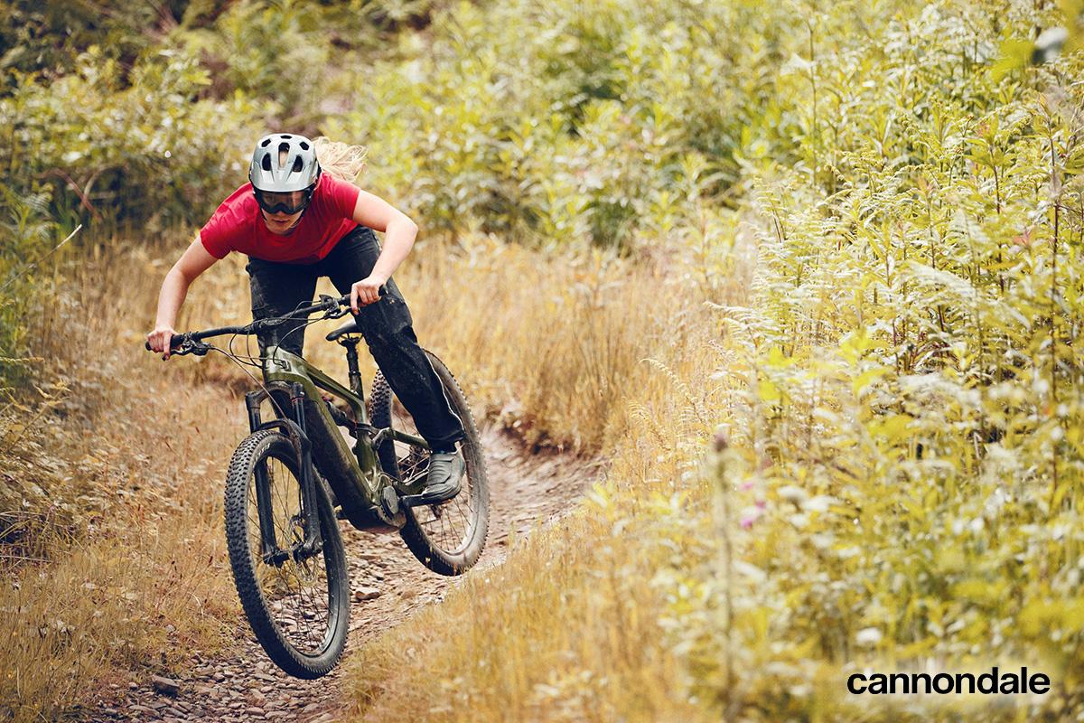 Un rider scende per una collina erbosa con una nuova emtb Cannondale 2021