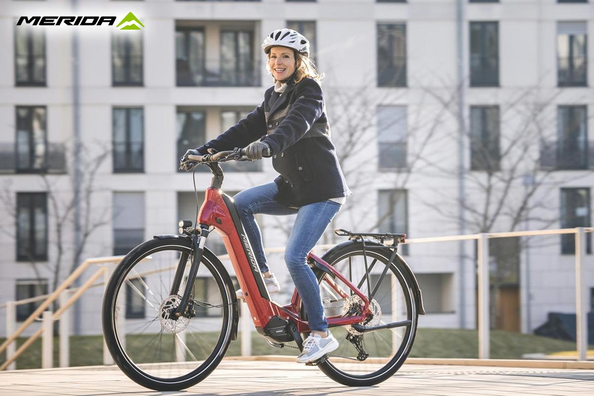 Una donna pedala in sella ad una nuova ebike da città Merida 2021