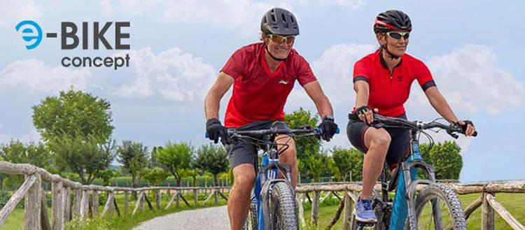 Un uomo e una donna a spasso in sella a biciclette elettriche